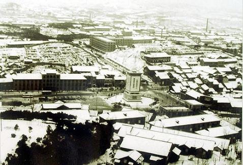 """上世纪70年代初期,拍摄者在东塔公园拍摄人民广场的全景照片。照片看到的是上南下北。毛主席的光辉形象塔矗立中央,东南有""""邵阳大饭店"""",南面有""""东风饭店"""",西面是运输公司,北面有新修的""""烹调大学""""。那时,南面的东区政府楼、外贸楼、工商银行和远处的黄家山新华书店都还没有修建。"""