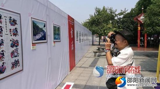 王雄杰老人正在书法美术摄影展上拍摄自己心仪的作品。 贺旭艳 摄