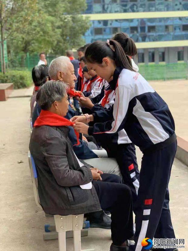 少先队员代表给退休教师们戴红领巾